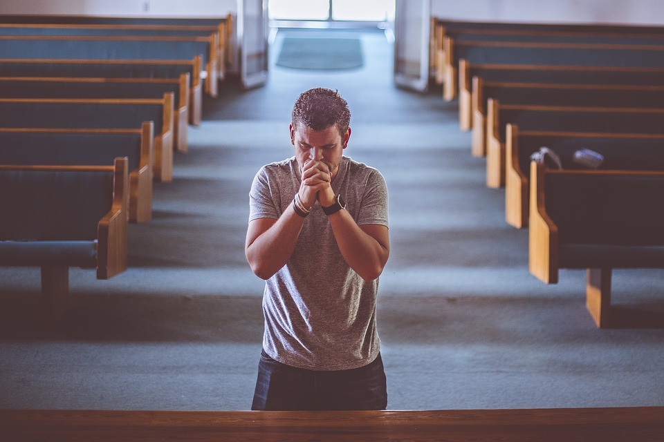this image shows a man praying inside saint hedwig church